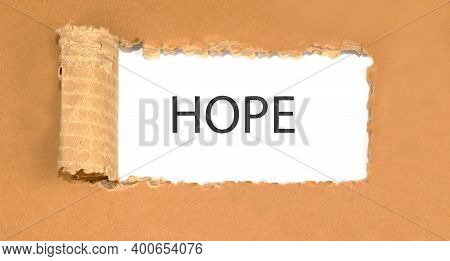 Text Hope Behind Torn Brown Paper. Torn Cardboard