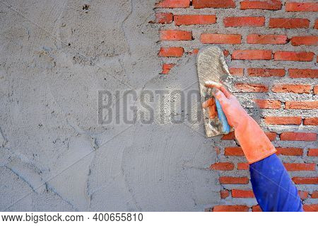 Plasterer Man's Hand In Blue Long Sleeve With Rubber Glove Using Wooden Trowel To Plastering Cement