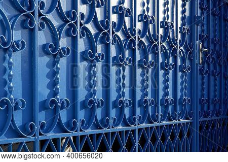 Sunlight And Shadow On Surface Of Wrought-iron Elements Pattern Of Vintage Blue Metal Gate Door Deco