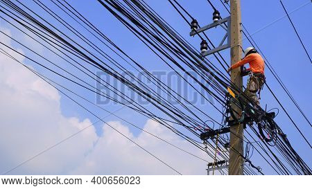 Low Angle View Of Electrician Lineman Working To Install Electrical System On Electric Power Pole Ag