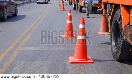 Row Of Traffic Cones With Low Section Of Crane Trucks Parking On Asphalt Road For Safety And Securit
