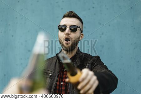 Bearded Cool Man Toasting Beer With Best Friend Outdoor Against A Blue Wall Background - Hands Of Hi