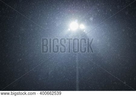 A Street Lamp Shines Through The Heavy Snowfall. Night, Lantern, Snowfall. Background Of Snowfall.