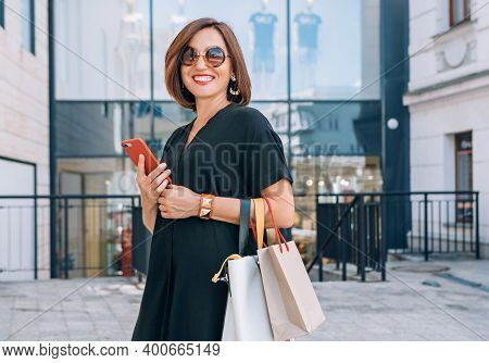 Smiling Beautiful Modern Middle-aged Female Portrait Dressed Black Dress And Sunglasses With Shoppin