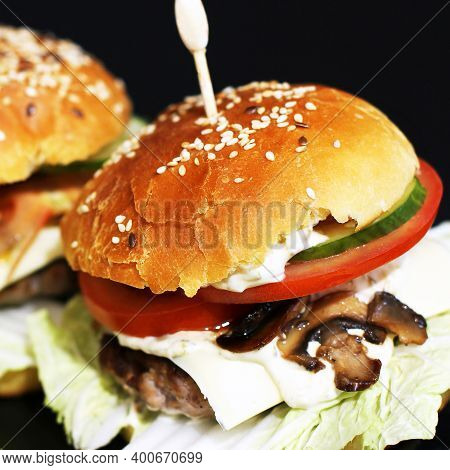 Homemade Juicy Burger. Home-made Fast Food. Bun With Sesame Seeds And Filling. Big Sandwich