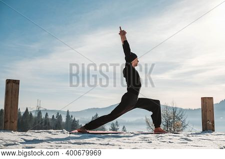 Caucasian Senior Man Doing Yoga Exercises In Front Of Amazing Sunset On The Winter Mountains. Copy,
