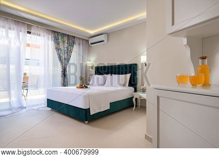 Elegant Modern Interior Of Bedroom In Double Suit Hotel Apartment With Soft Aquamarine Textile Bed,