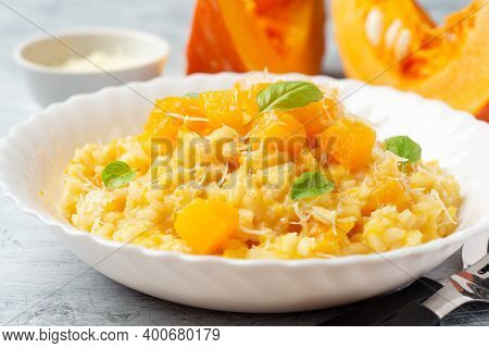 Pumpkin Risotto With Parmesan Cheese And Basil Leaves On Concrete Background