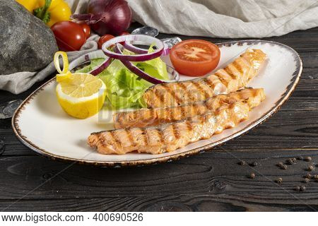 Grilled Salmon Steak With Salad, Onions And Tomatoes. Classic Hot Fish Dish Of Sea Fish, Vegetables