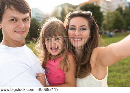 Young Family Man Woman And Child Daughter 5-7 Years Old, Summer Park, Selfie Photo On Phone, Outdoor