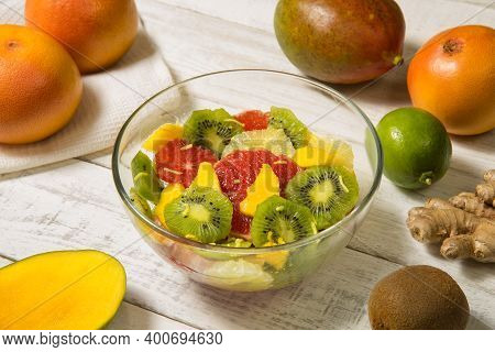 Vitamin C Super Fruit Salad In A Glass Bowl On A White Rustic Table With Ingredients. Close Up.