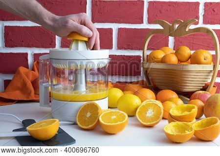 A Man Squeezes An Orange On A Juicer, Squeezed And Whole Oranges On The Table, Behind A Brick Wall