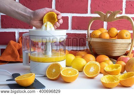A Man Squeezes An Orange On A White Juicer, Squeezed And Whole Oranges On The Table, Behind A Brick