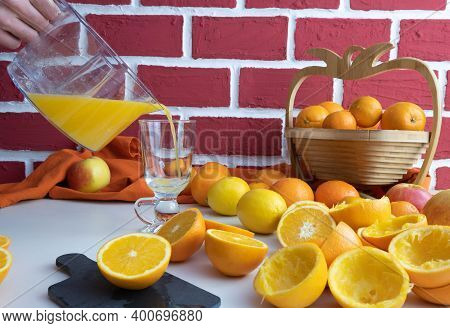 Freshly Squeezed Orange Juice Is Poured Into A Glass, Whole And Squeezed Oranges On The Table, Behin