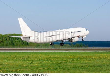 Take-off From The Airport Runway Of A White Passenger Airplane On A Clear Summer Day