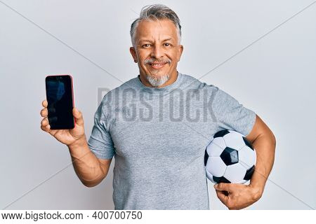 Middle age grey-haired man holding football ball showing smartphone smiling with a happy and cool smile on face. showing teeth.