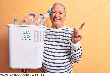 Senior handsome grey-haired man recycling holding wastebasket full of plastic bottles smiling happy pointing with hand and finger to the side