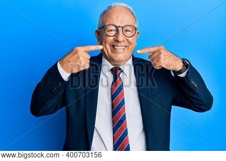 Senior caucasian man wearing business suit and tie smiling cheerful showing and pointing with fingers teeth and mouth. dental health concept.