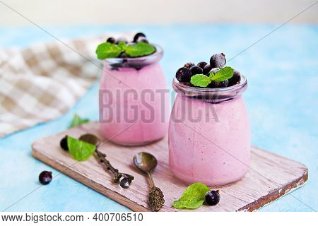 Dessert, Airy Mousse Whipped Cream And Mashed Black Currants In Portion Jars On Light Blue Backgroun