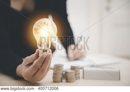 Business Hand Holding Light Bulb And Working On The Desk, Creativity And Innovation Are Keys To Succ