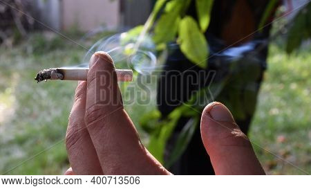 Closeup Of Flying Gray Smoke From Cigarette Holding In Dirty Fingers Of Male Hand At Outdoor Blurred