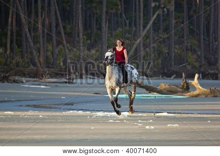 woman riding galloping horse bareback on the beach