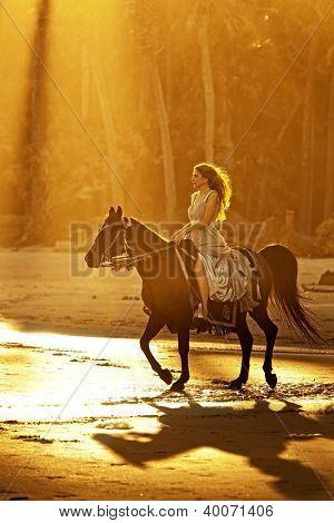 backlit woman on horseback in formal dress riding on beach