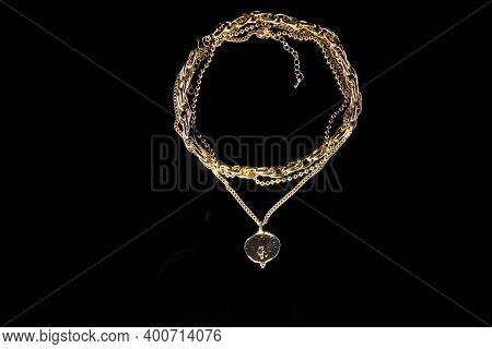 Golden Jewelry Chain With Medallion Isolated On Black Background