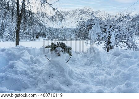 A Snowman On The Shore Of Lake Fusine, Tarvisio, Frozen In Winter