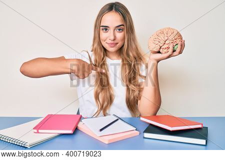 Young beautiful blonde woman holding brain while studying for school pointing finger to one self smiling happy and proud