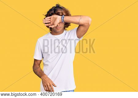 Young hispanic man wearing casual white tshirt covering eyes with arm, looking serious and sad. sightless, hiding and rejection concept
