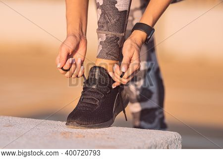 Close Up Of Sporty Fitness Woman Tying Shoelaces. Preparing For Workout