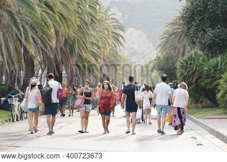 People Walking Along The Beach Wearing Protective Or Medical Face Masks. New Normal In Italy. People