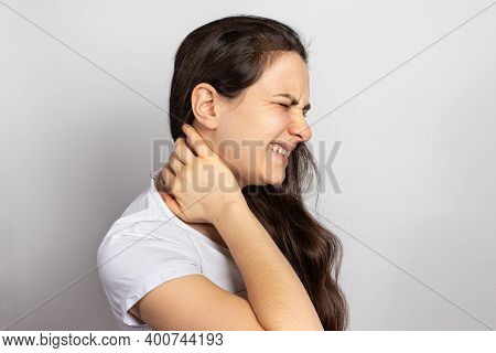 The Woman Had A Neck, Muscle Cramp And Tension. With A Place For Text On A Light Background. Osteoch