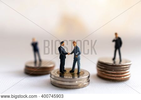 Miniature People: Businessman Handshake With Coins Stack On World Map,  Investment, Agreement, Partn
