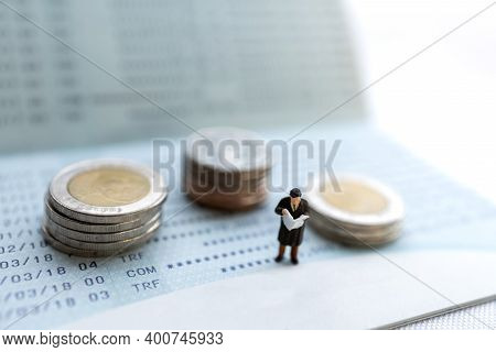 Miniature People Stand On The Bank Passbook And Coins Stack, Retirement Planning And Life Insurance