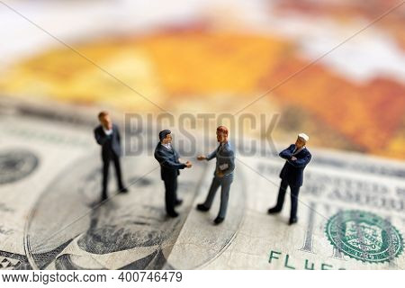 Miniature People: Businessman Handshake With Money On World Map,  Investment, Agreement, Partnership