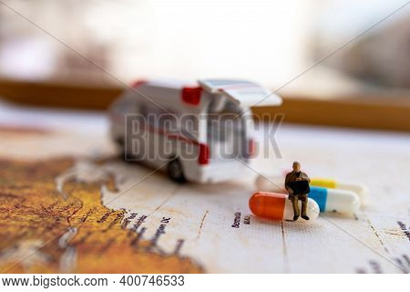 Miniature People : Patient Sitting On Capsule With Ambulance. Healthcare And Medical Concepts.