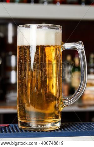 A Glass Of Fresh Foamy Beer On The Bar Counter