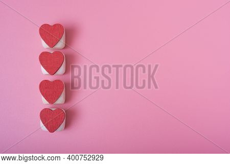 Four Red Hearts Vertically In A Row On The Left Side, Pink Background.