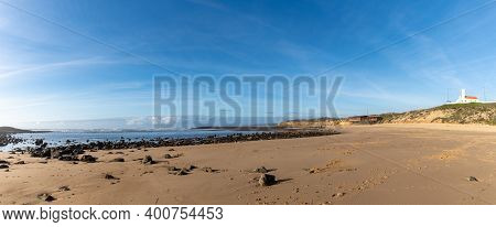 Panorama View Of The Praia Do Farol And Lighthouse In Milfontes