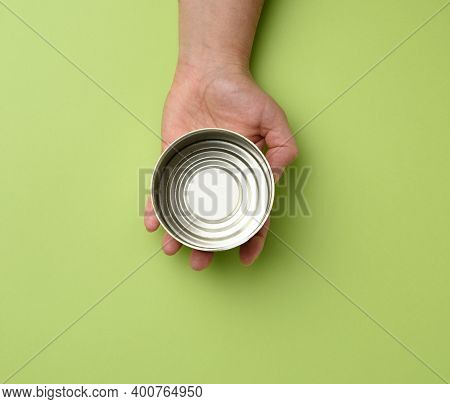 Open Metal Round Tin Can In A Female Hand On A Green Background, Top View