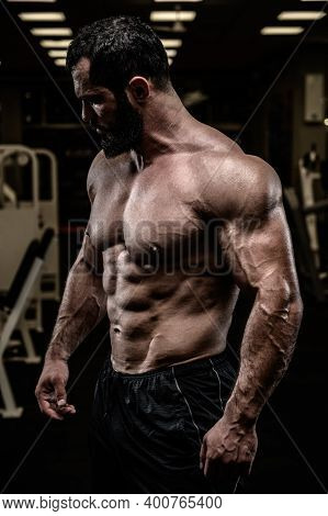Strong Young Bearded Caucasian Man With Sport Physique Body Torso Standing In Dark Fitness Gym With