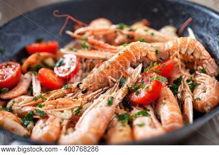 Scampi Cooked With Tomatoes And Parsley In A Pan