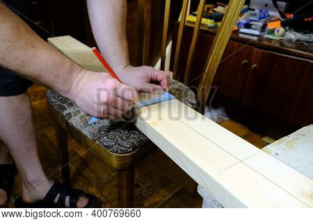A Man Marks A Board With A Pencil Using A Square. Do It Yourself. Home Repair Concepts, Close Up.
