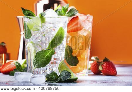 Fresh Mojito Cocktail Set With Lime, Mint, Strawberry And Ice In Glass On Orange Background. Summer