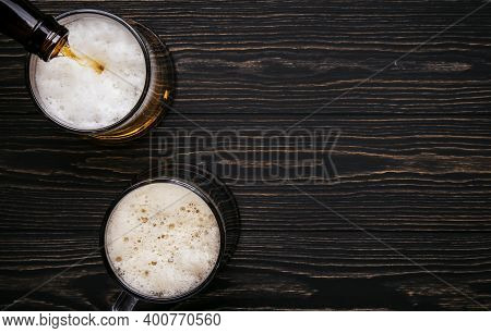 Dark Beer, Ale Or Stout Is Poured Into Glass, Dark Wooden Bar Counter, Space For Text, Top View