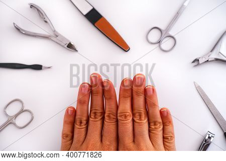 Woman's Hands With Uncoated Manicure And Home Manicure Tools. White Background.