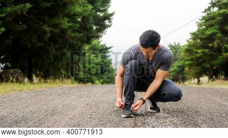Men Knelt Down To Do Up His Shoelaces Prepare Exercise In The Morning.