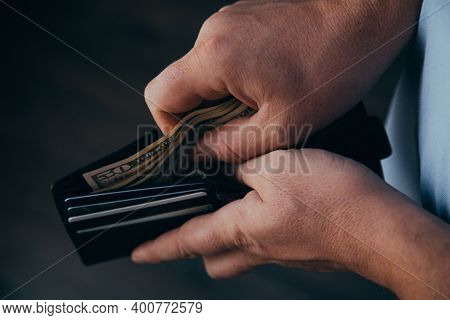 Hands Of A Working Man Counting Dollar Bills In An Empty Wallet. Poverty Concept. Dismissal Or Accum